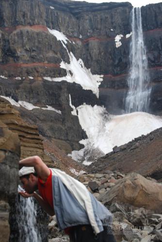 Jorge bebiendo agua pura frente a la gran catarata de Hengifoss tras un gran trekking.