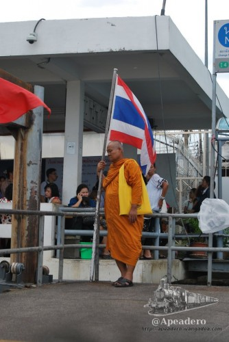 Todo un emblema de Tailandia, un monje apoyado en una bandera, solo le falta la foto del rey