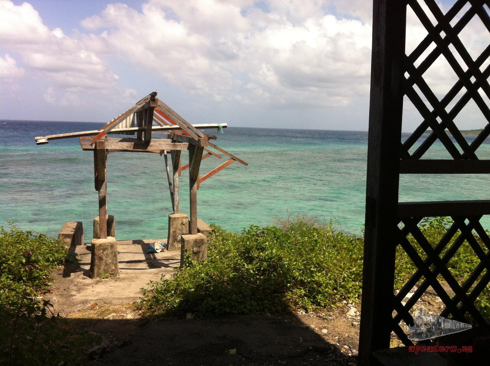 """Esa especie de atechado incompleto marca el lugar dónde están las primeras escaleras de acceso a la zona de snorkeling. Toda esta zona era un viejo hotel que ahora está en horas bajas. Aunque ponga un rótulo de """"hotel"""" entrad sin miedo, ya no está, solo quedan algunos edificios."""