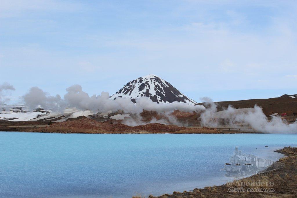 La impresionante laguna azul con el vapor de la factoría y un volcán al fondo.